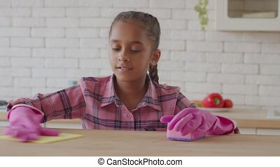 Industrious african girl polishing kitchen table - Cute ...