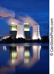 industry at night - a smoking industrial power plant at...