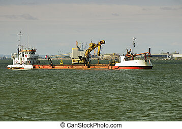Offshore oil and gas platform supply vessel underway, and machine for drilling holes in the sea in port Spain