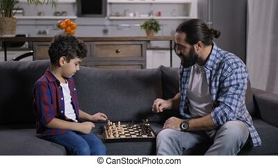 Inetelligent father teaching son to play chess