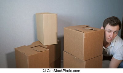 inexperienced young delivery service man takes a lot of cardboard box and boxes falling