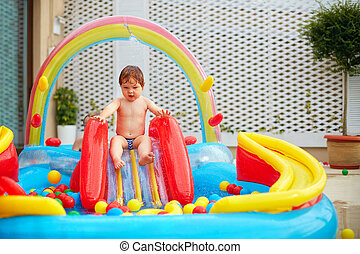 infant baby boy are going to slide in inflatable pool at the patio zone