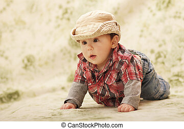 Infant baby in a hat on a green background
