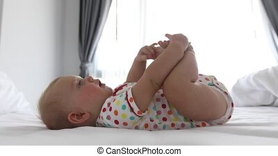 Infant baby lying on white bed - Side view of happy baby in...
