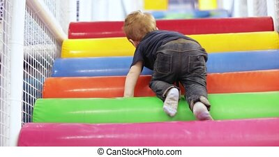 Infant boy plays on a plastic slide