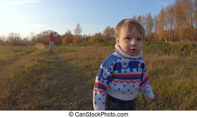 Infant boy running away from mom walking on the edge of the forest