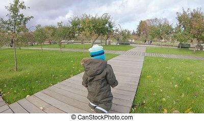 Infant boy runs along the path