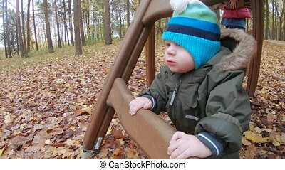 Infant boy stands wooden staircase