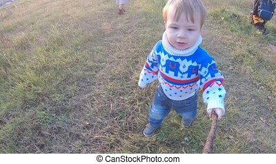 Infant boy walking along a path and holding on to a stick