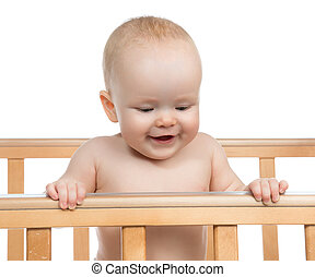 Infant child baby boy in wooden bed looking down on white...