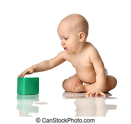 Infant child baby boy toddler sitting in diaper playing with green brick toy