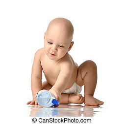 Infant child baby boy toddler sitting in diaper try to take a bottle of water isolated on a white