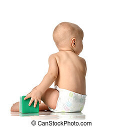 child baby boy toddler sitting in diaper with green brick toy from behind rear backside view isolated on a white
