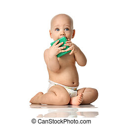 Infant child baby boy toddler sitting in diaper with green brick toy looking up