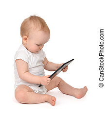 Infant child baby toddler sitting and typing digital tablet mobile computer isolated on a white background