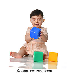 Infant child baby toddler sitting in dress with green blue and yellow brick toy playing isolated on a white