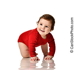 Infant child boy toddler in red body cloth learning crawling happy smiling