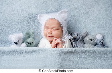 Infant child in bonnet with ears sleeping with toys