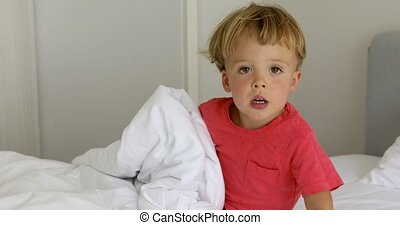 Infant child on white bed - Adorable little boy sitting on...