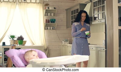 Infant Food - Slow motion of pretty mother preparing food...