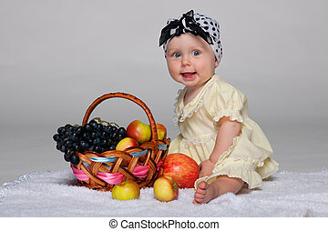 Infant girl near the basket with vegetables
