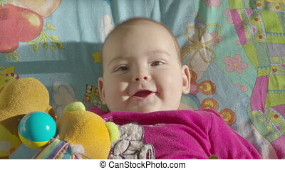 Infant girl playing with developing toys lying in bed. Top view