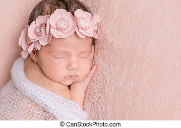 infant girl sleeping on a pink background