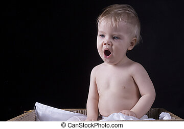 Infant is yawling on a black background