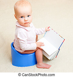 Little baby girl sitting on blue potty with open book
