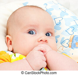 Infant with hands in mouth - Portrait of attentive cute...