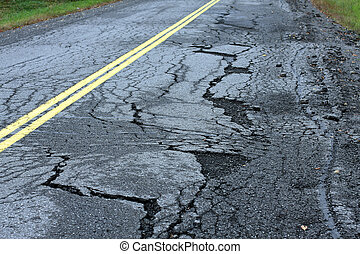 Infastructure Breakdown - Broken pavement and potholes on...