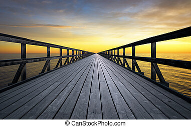 Long pier disappearing into orange sunset