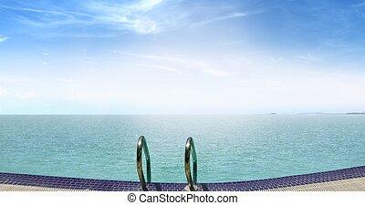 Infinity swimming pool facing sea at sunrise