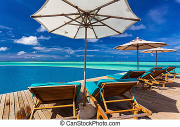 Infinity swimming pool on the beach of tropical island with white beach umbrellas