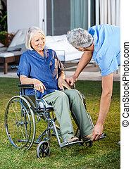 infirmière, ajustement, repose-pied, pour, femme aînée, sur, fauteuil roulant