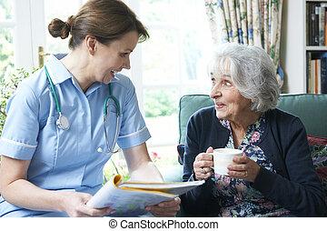 infirmière, discuter, notes médicales, à, femme aînée, chez soi