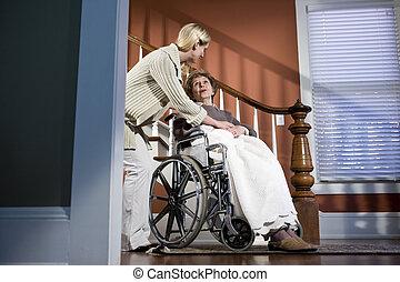 infirmière, portion, femme âgée, dans, fauteuil roulant, chez soi