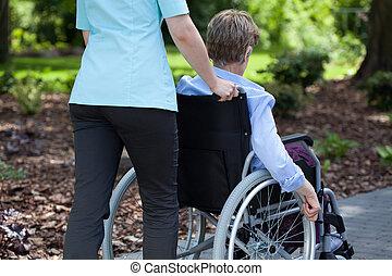 infirmière, pousser, femme âgée, sur, fauteuil roulant