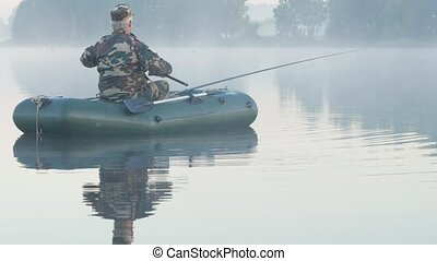 Inflatable boat with a male fisherman on a lake in the fog....