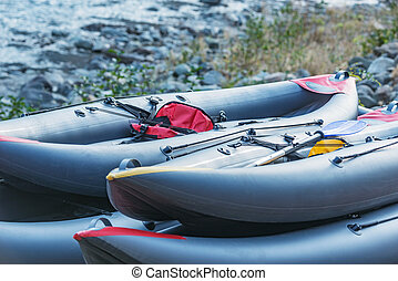 Inflatable boats on the mountain river shore.