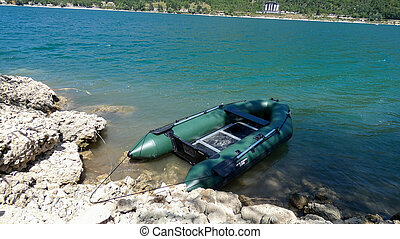 inflatable fishing boat on the water near the shore