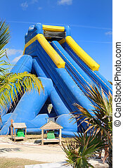 Inflatable Waterslide - Inflatable waterslide on a tropical...