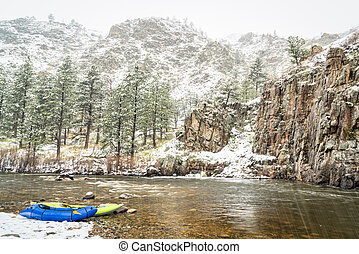 inflatable whitewater kayak and packraft in snowstorm - ...