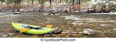 inflatable whitewater kayak in spring snowstorm - inflatable...