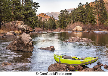 inflatable whitewater kayak on a mountain river - sunset...