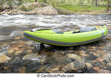 inflatable whitewater kayak on mountain river - inflatable...