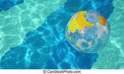 Inflated ball floats on wavy water surface in pool