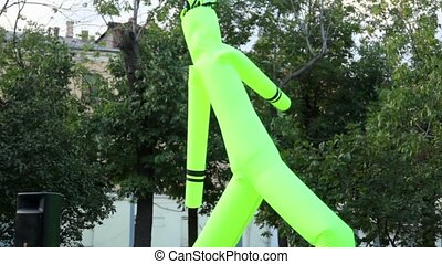 Inflated man dance at background of trees on City Day -...