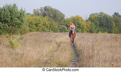 Inflated man with a strong physique rides a horse on the field from the forest, slow motion