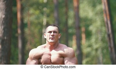 Inflated man workouts in the summer forest - huge biceps,...